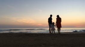 Den lyckliga familjen har gyckel på stranden lager videofilmer