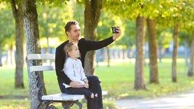 Den lyckliga familjen har gyckel som tar selfie på härlig höstdag lager videofilmer