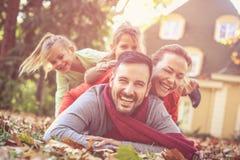 Den lyckliga familjen har gyckel tillsammans på husträdgården fotografering för bildbyråer