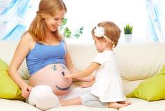 Den lyckliga familjen i förväntan av behandla som ett barn gravid barnmoder Royaltyfri Fotografi