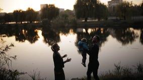 Den lyckliga familjen i höst parkerar mot bakgrunden av sjön, konturerna stock video
