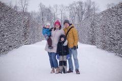 Den lyckliga familjen i kall vinter parkerar att bli tillsammans arkivbild