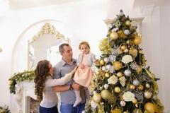 Den lyckliga familjen i lycklig förväntan av ferie står tillsammans nea Royaltyfri Fotografi