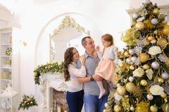 Den lyckliga familjen i lycklig förväntan av ferie står tillsammans nea Royaltyfri Bild
