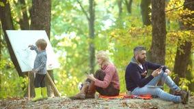 Den lyckliga familjen i soligt parkerar Lycklig tidsf?rdriv tillsammans Sund och lycklig tid med familjen Rolig playgame med fami arkivfilmer