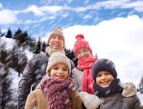 Den lyckliga familjen i vinter beklär utomhus Arkivbild