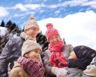 Den lyckliga familjen i vinter beklär utomhus Arkivfoton