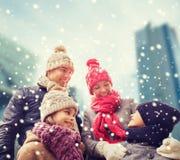 Den lyckliga familjen i vinter beklär utomhus Arkivfoto