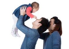 Den lyckliga familjen kastar behandla som ett barn upp dottern royaltyfria bilder
