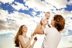 Den lyckliga familjen kastar behandla som ett barn upp pojken mot blå himmel Arkivfoton