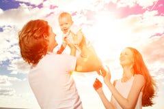 Den lyckliga familjen kastar behandla som ett barn upp pojken mot blå himmel Arkivbild