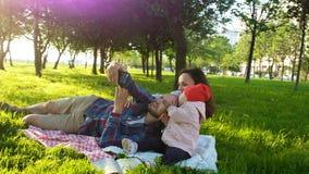 Den lyckliga familjen lägger på plädet och gör selfie med en behandla som ett barn på solnedgången i parkera Fadern och modern ta royaltyfri foto
