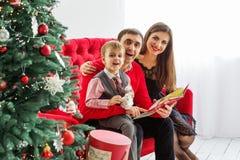 Den lyckliga familjen läser en bok nära en julgran Arkivbild