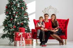 Den lyckliga familjen läser en bok nära en julgran Arkivfoto