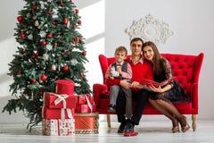 Den lyckliga familjen läser en bok nära en julgran Royaltyfri Fotografi