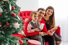 Den lyckliga familjen läser en bok nära en julgran Arkivfoton