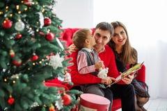 Den lyckliga familjen läser en bok nära en julgran Arkivbilder