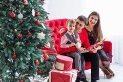 Den lyckliga familjen läser en bok nära en julgran Royaltyfria Foton