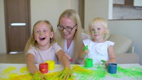 Den lyckliga familjen målar färger Den lyckliga familjen målar färger Modern och dottern som har gyckel och, målar sig ` s på fra stock video