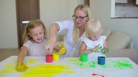 Den lyckliga familjen målar färger Lyckliga små childs som gör färgrik färghandsprint på vitboken Lite gulligt lyckligt lager videofilmer