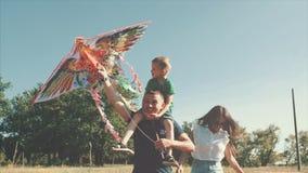 Den lyckliga familjen, mamman, farsan och sonen går i naturen som lanserar en luftorm Materiellängd i fot räknat stock video