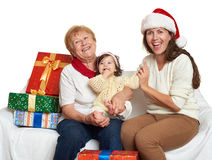 Den lyckliga familjen med askgåvan, kvinnan med barnet och åldring - semestra begreppet Royaltyfri Fotografi