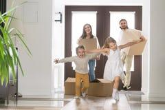 Den lyckliga familjen med barn ankom på deras nya hus royaltyfria foton