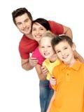 Den lyckliga familjen med barn som tillsammans står i, fodrar Fotografering för Bildbyråer