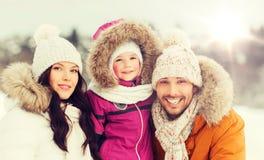 Den lyckliga familjen med barnet i vinter beklär utomhus royaltyfri bild
