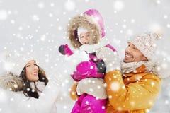 Den lyckliga familjen med barnet i vinter beklär utomhus royaltyfri fotografi