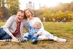 Den lyckliga familjen med barnet som har gyckel i höst, parkerar sammanträde på en pläd fotografering för bildbyråer
