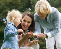 Den lyckliga familjen med behandla som ett barn modern och farmodern utomhus Arkivbild