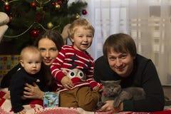 Den lyckliga familjen med behandla som ett barn under den dekorerade julgranen, gåvor Arkivbild