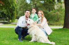 Den lyckliga familjen med den labrador retriever hunden parkerar in Arkivfoton