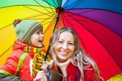 Den lyckliga familjen med det färgrika paraplyet i höst parkerar Arkivbild