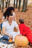 Den lyckliga familjen med det lilla gulliga barnet parkerar in på det gula bladet med fotografering för bildbyråer