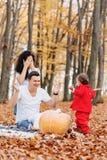 Den lyckliga familjen med det lilla gulliga barnet parkerar in på det gula bladet med royaltyfri fotografi
