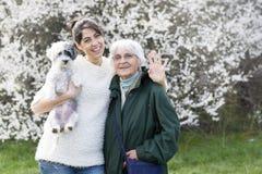 Den lyckliga familjen med en hund i en vår parkerar fotografering för bildbyråer