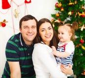 Den lyckliga familjen med jul behandla som ett barn nära julgranen Royaltyfri Fotografi
