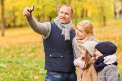 Den lyckliga familjen med kameran i höst parkerar Royaltyfria Bilder