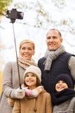 Den lyckliga familjen med smartphonen och monopod parkerar in Royaltyfri Fotografi