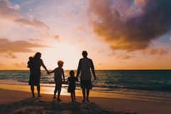 Den lyckliga familjen med trädungar går på solnedgångstranden royaltyfria foton