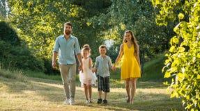 Den lyckliga familjen med två barn som rymmer händer under fritids-, går royaltyfria foton