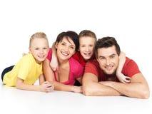 Den lyckliga familjen med två barn som ligger på vit, däckar Arkivfoto