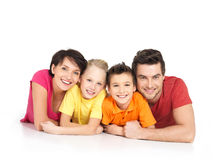 Den lyckliga familjen med två barn som ligger på vit, däckar Arkivbild