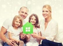 Den lyckliga familjen med två ungar och papper inhyser hemma Royaltyfri Fotografi