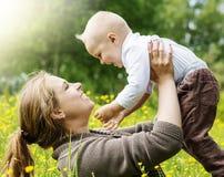 Den lyckliga familjen, moder lyfter hennes son på naturbakgrund Arkivfoton