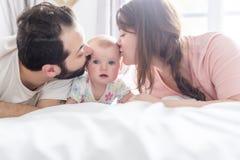 Den lyckliga familjen, modern, fader och behandla som ett barn på den vita sängen som ger sidokyssen royaltyfria bilder