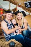 Den lyckliga familjen, modern, fadern och den lilla sonen piratkopierar in hattar Royaltyfria Bilder