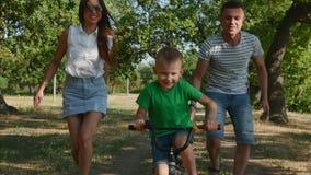 Den lyckliga familjen, modern, fadern och sonen går av naturen, barnet rider en cykel, hans föräldrar hjälper honom till stock video